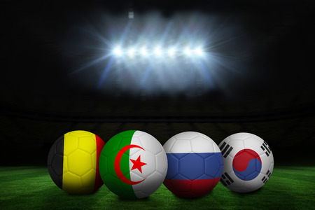 Composite image of footballs in group h colours for world cup against football pitch under spotlights photo