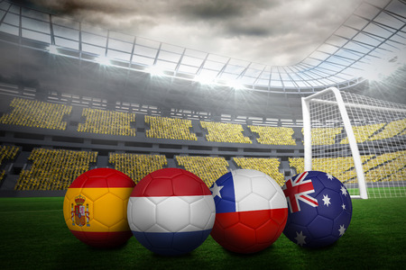 Composite image of footballs in group b colours for world cup against large football stadium with lights photo
