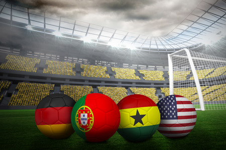 Composite image of footballs in group g colours for world cup against large football stadium with lights photo