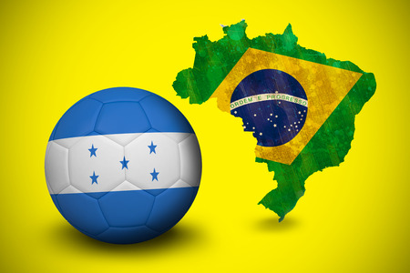 Football in honduras colours  against green brazil outline with flag on yellow photo