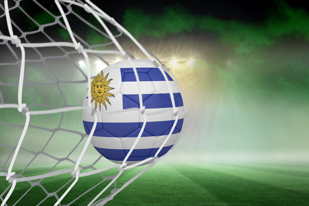 Football in uruguay colours at back of net against football pitch under green sky and spotlights photo