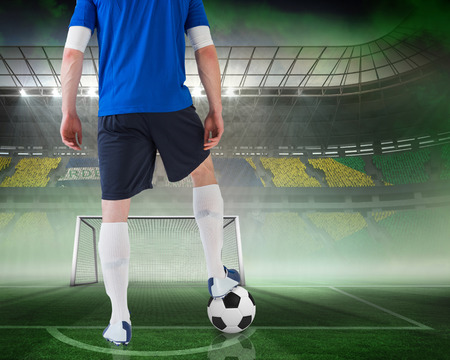 goalpost: Composite image of football player standing with ball against vast football stadium for world cup