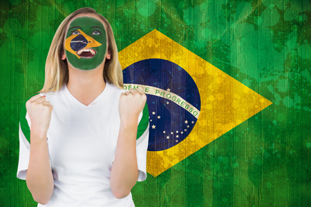 Excited brasil fan in face paint cheering against brazil flag in grunge effect photo