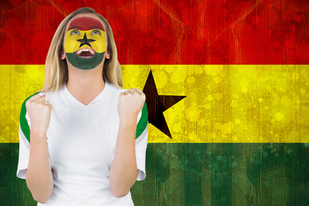 Excited ghana fan in face paint cheering against ghana flag in grunge effect photo
