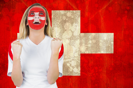 Excited fan in swiss face paint cheering against switzerland flag in grunge effect photo