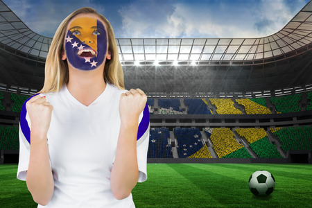 Excited bosnia fan in face paint cheering against large football stadium with brasilian fans photo