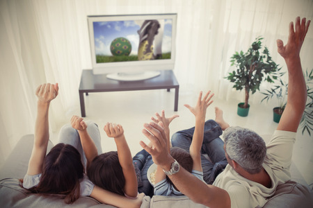 Family cheering and watching the world cup at home in the living room photo