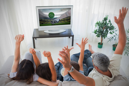 domiciles: Family cheering and watching the world cup at home in the living room