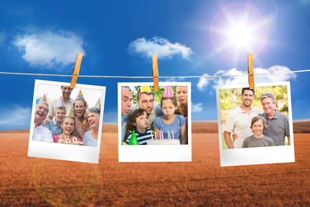 Composite image of instant photos hanging on a line against field and blue sky photo