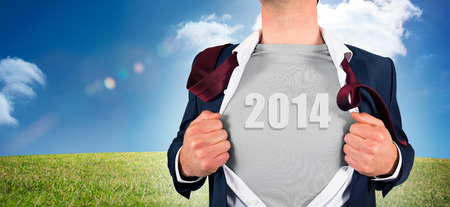 Businessman opening shirt in superhero style against digital landscape photo