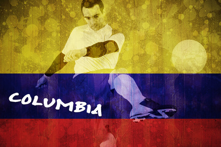 Football player in yellow kicking against colombia flag in grunge effect photo