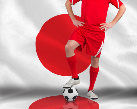 Composite image of football player standing with ball against digitally generated japan national flag photo