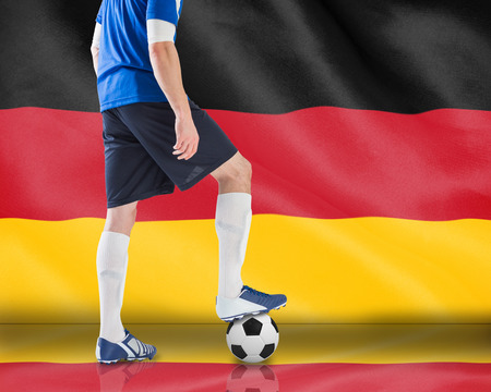 Composite image of football player standing with ball against digitally generated german national flag photo