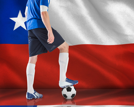 Composite image of football player standing with ball against digitally generated chile national flag photo