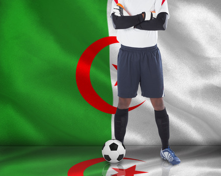 Composite image of goalkeeper in white with ball against algerian flag photo