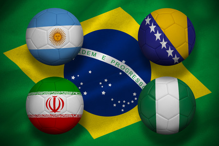 Composite image of group f footballs for world cup against digitally generated brazilian national flag photo