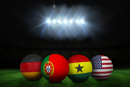 Composite image of footballs in group g colours for world cup against football pitch under spotlights photo