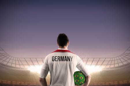 Germany football player holding ball against large football stadium under blue sky photo