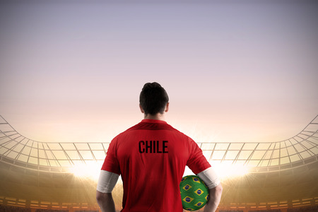 Chile football player holding ball against large football stadium under blue sky photo
