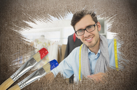 composite image: Composite image of fashion designer smiling at camera with paintbrush dipped in blue against weathered surface  Stock Photo