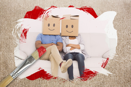 Composite image of couple wearing boxes on head with paintbrush dipped in red against weathered surface  photo