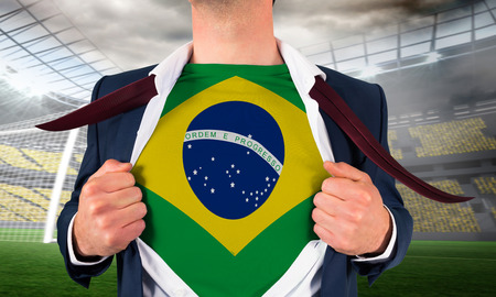 Businessman opening shirt to reveal brasil flag against large football stadium with lights photo