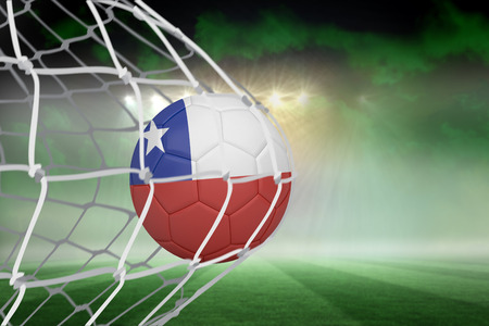 Football in chile colours at back of net against football pitch under green sky and spotlights photo