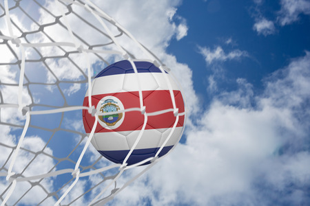 Football in costa rica colours at back of net against bright blue sky with clouds photo
