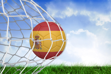 Football in spain colours at back of net against field of grass under blue sky photo