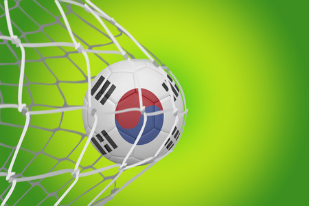 Football in south korea colours at back of net against green vignette photo