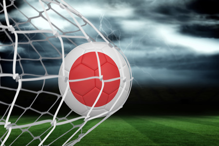 Football in japan colours at back of net against football pitch under stormy sky photo