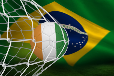 Football in ivory Coast colours at back of net against brazilian flag waving photo