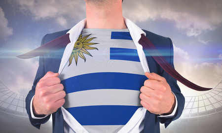 Businessman opening shirt to reveal uruguay flag against large football stadium under cloudy blue sky photo