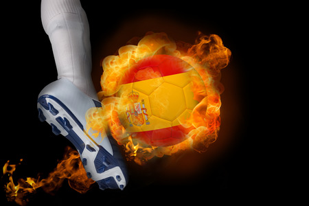 Football player kicking flaming spain ball against black photo