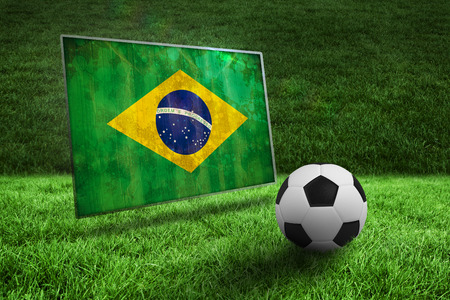 Black and white football on grass against brazil flag in grunge effect photo