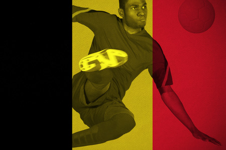 Football player in red kicking against belgium national flag photo