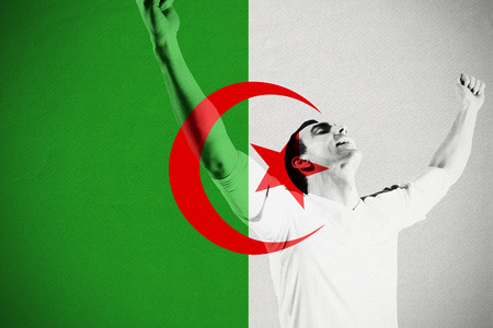 Excited football fan cheering against algeria national flag photo