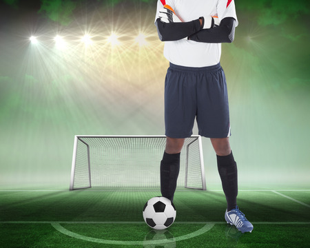 goalpost: Composite image of goalkeeper standing with ball against football pitch and goal under spotlights