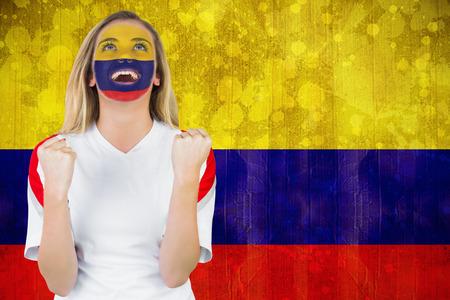 bandera de colombia: Emocionado fan Colombia en la cara de pintura vítores contra la bandera Colombia en efecto grunge Foto de archivo