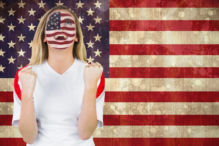 Excited fan in usa face paint cheering against usa flag in grunge effect photo