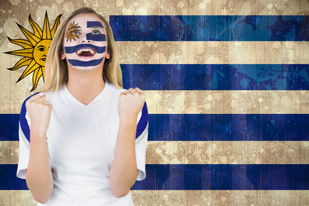 Excited fan in uruguay face paint cheering against uruguay flag in grunge effect photo