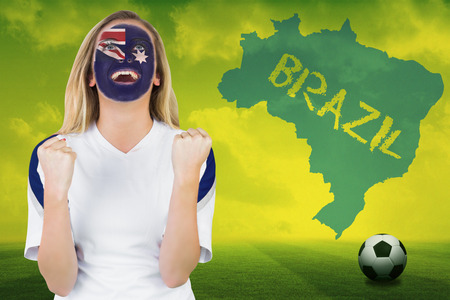 Excited australia fan in face paint cheering against football pitch with brazil outline and text photo