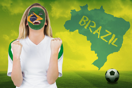 Excited brasil fan in face paint cheering against football pitch with brazil outline and text photo