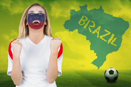 Excited russia fan in face paint cheering against football pitch with brazil outline and text photo