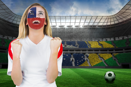 Excited chile fan in face paint cheering against large football stadium with brasilian fans photo