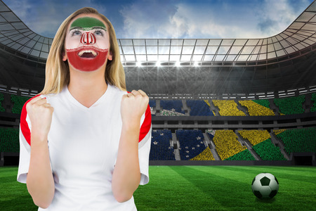 Excited iran fan in face paint cheering against large football stadium with brasilian fans photo