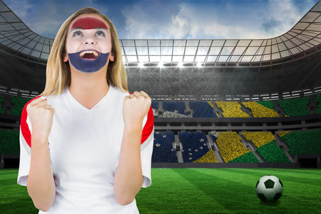 Excited netherlands fan in face paint cheering against large football stadium with brasilian fans photo