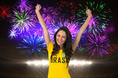 Excited football fan in brasil tshirt against fireworks exploding over football stadium photo
