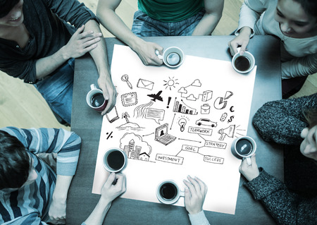 People sitting around table drinking coffee with page showing brainstorm graphic photo
