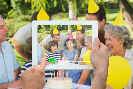 Hand holding tablet pc showing extended family wearing party hats at birthday celebration in park photo